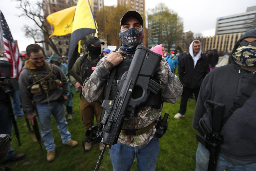 In this April 30, 2020, file photo, a protester carries his rifle at the State Capitol in Lansing, Mich. (AP Photo/Paul Sancya, File)