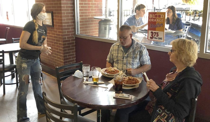 Anna Barnard, left, wears a protective mask as she talks to Greg and Judy Robinson at Dugan's Pub in Little Rock, Arkansas on Monday, May 11,2020. Restaurants in Arkansas were allowed to resume offering dine-in service on Monday after they had been limited to delivery or carryout because of the coronavirus pandemic. (AP Photo/Andrew DeMillo)