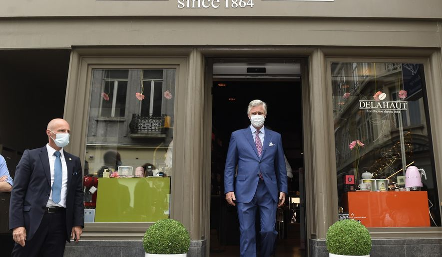 Belgium's King Philippe, center, wearing a mouth mask, leaves a shop after a royal visit in Brussels, Sunday, May 10, 2020. The Belgian King Philippe visited several shops on Sunday, one day ahead of a re-opening on Monday when some lockdown measures against the spread of coronavirus, COVID-19 will be relaxed and many shops will be able to open their doors. (Didier Lebrun, Pool Photo via AP)
