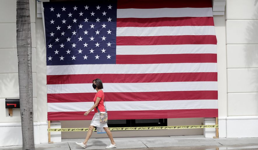 A woman wearing a protective face mask walks past an American flag in front of a closed business during the new coronavirus pandemic, Monday, May 11, 2020, in Palm Beach, Fla. Palm Beach County was authorized by Florida Gov. Ron DeSantis to initiate Phase 1 reopening regulations Monday, which includes limited reopening of retail establishments. (AP Photo/Lynne Sladky)