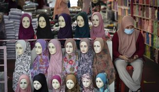 A shop vendor wearing a face mask to help curb the spread of the coronavirus waits for customer outside headscarves shop in Kuala Lumpur, Malaysia, on Monday, May 11, 2020. Despite a sharp drop in infections, Malaysia's leader said restrictions to fight the coronavirus will be extended by four more weeks until June 9. The government has already let most businesses reopen with strict conditions to help revive a hard-hit economy. But mass gatherings are still barred, with schools, cinemas and houses of worship staying shut, group sports prohibited and interstate travel banned. (AP Photo/Vincent Thian)