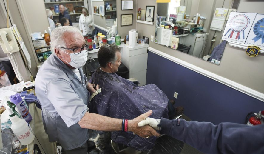 Karl Manke, owner of Karl Manke Barber Shop in Owosso, Mich., left, shakes hands with a customer while giving John Taschner of Novi a haircut, Monday, May 11, 2020. Manke has defied the governor's not to conduct business. (Matthew Dae Smith/Lansing State Journal via AP)