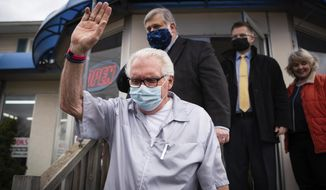Karl Manke, 77, waves to people gathered just before a press conference on Monday, May 11, 2020 at Karl Manke's Beauty & Barber Shop in Owosso, Mich. Manke has defied the governor's order not to conduct business. (Sarahbeth Maney/The Flint Journal via AP)