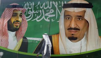 FILE - In this March 7, 2020 file photo, a man walks past a banner showing Saudi King Salman, right, and his Crown Prince Mohammed bin Salman, outside a mall in Jiddah, Saudi Arabia. Saudi Arabia announced Monday, May 11, 2020, it is tripling taxes on basic goods to 15% and will cut spending on major projects by around $26 billion as it grapples with blows from the coronavirus pandemic and low oil prices on its economy. (AP Photo/Amr Nabil, File)