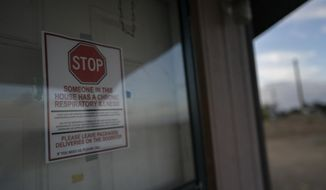 A sign is posted on the door of the hogan, a traditional Navajo dwelling, of Mabel Charley's home-bound uncle, to keep visitors out in Chilchinbeto, Ariz., on the Navajo reservation on April 21, 2020. The reservation has some of the highest rates of coronavirus in the country. If Navajos are susceptible to the virus' spread in part because they are so closely knit, that's also how many believe they will beat it. (AP Photo/Carolyn Kaster)