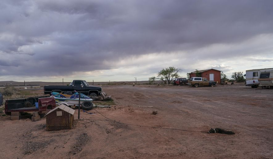 A dog sleeps on the red sand on the end of his chain at the Dinehdeal family compound in Tuba City, Ariz, on the Navajo reservation on April 20, 2020. The Dinehdeal family has been devastated by COVID-19. (AP Photo/Carolyn Kaster)