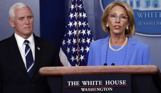 Education Secretary Betsy DeVos speaks about the coronavirus in the James Brady Press Briefing Room, Friday, March 27, 2020, in Washington, as Vice President Mike Pence listens. (AP Photo/Alex Brandon)