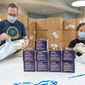 JOOLA employees John Miller and Caroline Kajihahra prepare a shipment of face masks at the company's headquarters in Rockville, Maryland. The table tennis supply distributor has sold more than 3 million masks to health care providers. (JOOLA)