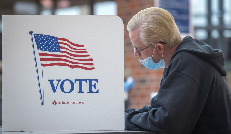 Chuck Schweitzer votes with a mask at a voting booth during Nebraska primary election in Lincoln, Neb., Tuesday, May 12, 2020. (Justin Wan/Lincoln Journal Star via AP)