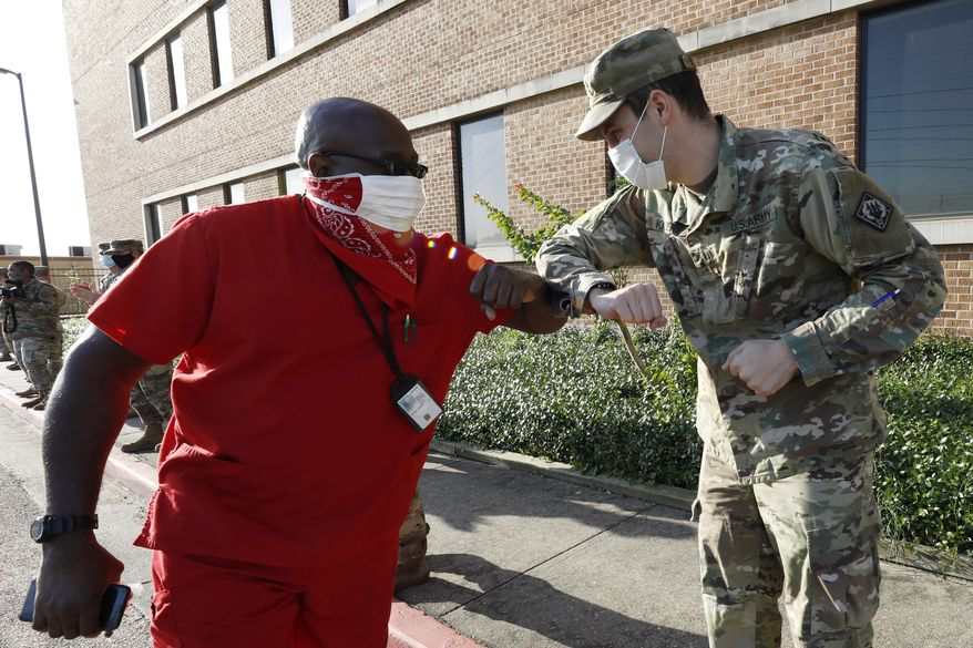 Mississippi Army National Guard Sgt. Newman Kazery, right, elbow bumps with Charles Jenkins, a supply tech and disabled Navy veteran, as he goes to work at the G.V. (Sonny) Montgomery VA Medical Center in Jackson, Miss., Tuesday, May 12, 2020. Kazery was one of 50 members of the Mississippi Air and Army National Guard that stood outside the medical facility and applaud both incoming and outgoing medical shifts honoring medical personnel for their efforts in working with the coronavirus on the final day of National Nurses Week. (AP Photo/Rogelio V. Solis)