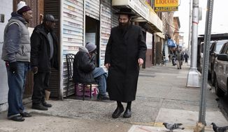 In this Dec. 13, 2019, file photo, A Jewish man, right, walks along Martin Luther King Drive in Jersey City, N.J., near the location where three people and two gunmen were shot and killed earlier in the week. American Jews were targets of more anti-Semitic incidents in 2019 than any other year over the past four decades, a surge marked by deadly attacks on a California synagogue, a Jewish grocery store in New Jersey and a rabbi's New York home, the Anti-Defamation League reported Tuesday, May 12, 2020. (AP Photo/Mark Lennihan, File)