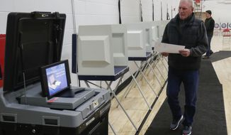 Mark Spear makes his way to the voting machine after filling out his ballot during a special election for Wisconsin's 7th Congressional District on Tuesday, May 12, 2020, at Wausau East High School in Wausau, Wis. Republican Tom Tiffany and Democrat Tricia Zunker are vying to fill the vacancy left by Republican Sean Duffy, who resigned from the seat in September. (Tork Mason/The Post-Crescent via AP)