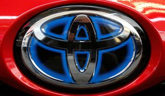 FILE- This Feb. 15, 2018, file photo shows the Toyota logo on the trunk of a 2018 Toyota Prius on display at the Pittsburgh Auto Show. Toyota Motor Corp. reported Tuesday, May 12, 2020 a sharp plunge in fiscal fourth quarter profit as the global pandemic slammed vehicle sales and halted production at its auto plants. (AP Photo/Gene J. Puskar, File)
