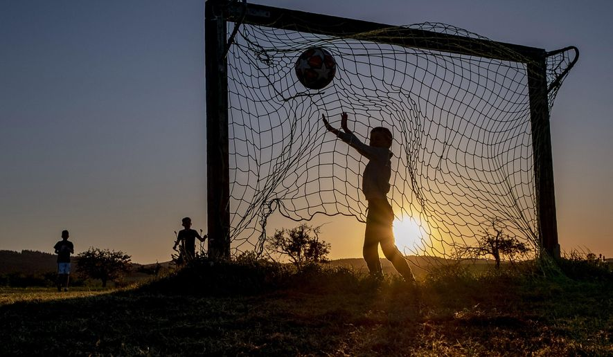 Children play soccer on a meadow with makeshift goals in Obernhain near Frankfurt, Germany, Tuesday, May 5, 2020. Due to the coronavirus playgrounds in German were closed until last Monday. (AP Photo/Michael Probst)