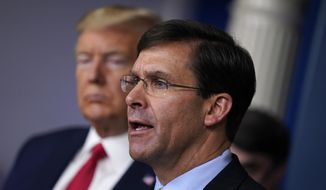 In this March 18, 2020, photo, Defense Secretary Mark Esper speaks as President Donald Trump listens during a press briefing with the coronavirus task force, at the White House in Washington. (AP Photo/Evan Vucci) **FILE**