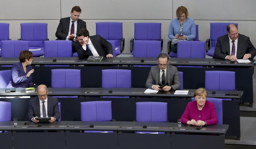 FILE - In this Thursday, April 23, 2020 file photo, German Chancellor Angela Merkel, front right, and ministers of the German government attend a meeting of the German federal parliament, Bundestag, at the Reichstag building in Berlin, Germany. Across Europe and beyond, parliaments and governments have had to adapt their operations to stop the virus spreading through the corridors of power. Social distancing, online debates, masks, plexiglass, hazard tape, each country's legislature has its own measures. (AP Photo/Michael Sohn, File)