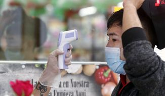 Amid concerns of the spread of COVID-19, Ronaldo Santos has his temperature checked before starting his work shift in the meat department of a grocery store in Dallas, Tuesday, May 12, 2020. The US is tracking 1000s of new cases daily as workplace worries mount with more businesses reopening. (AP Photo/LM Otero)