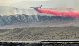FILE - In this Aug. 14, 2015, file photo, a plane tries to help put out a wildfire burns near the Reynolds Creek area in the Owyhee Mountains, Idaho. Authorities have approved a plan to prevent giant rangeland wildfires in southwestern Idaho by clearing vegetation along 435 miles of roads to create fuel breaks. The U.S. Bureau of Land Management last week approved the work for the Idaho portion of the Tri-state Fuel Breaks Project that also includes fuel breaks in southeastern Oregon and northern Nevada. (Adam Eschbach/The Idaho Press-Tribune via AP, File)