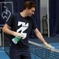 French veteran Nicolas Mahut cleans the net during a training session in the French Tennis Federation center near the grounds of the French Open in Paris, Wednesday, May 13, 2020 under the watchful eye of a team doctor and courtside trainers. Professional tennis players resumed training in France after the end of lockdown amid the coronavirus pandemic. (AP Photo/Francois Mori)