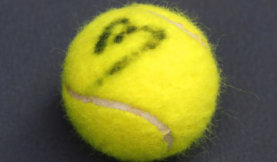 The tennis ball of french veteran Nicolas Mahut is marked with a sign during a training session in the French Tennis Federation center near the grounds of the French Open in Paris, Wednesday, May 13, 2020 under the watchful eye of a team doctor and courtside trainers. Professional tennis players resumed training in France after the end of lockdown amid the coronavirus pandemic. (AP Photo/Francois Mori)