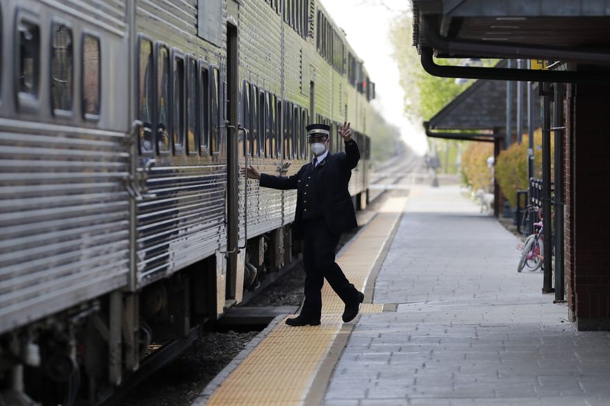 A Metra conductor signals for all clear at the Glenview Amtrak/Metra Station in Glenview, Ill., Wednesday, May 13, 2020. All customers are now required to wear a mask or face covering while using Metra, a commuter rail system in the Chicago metropolitan area serving the city of Chicago and surrounding suburbs. (AP Photo/Nam Y. Huh)
