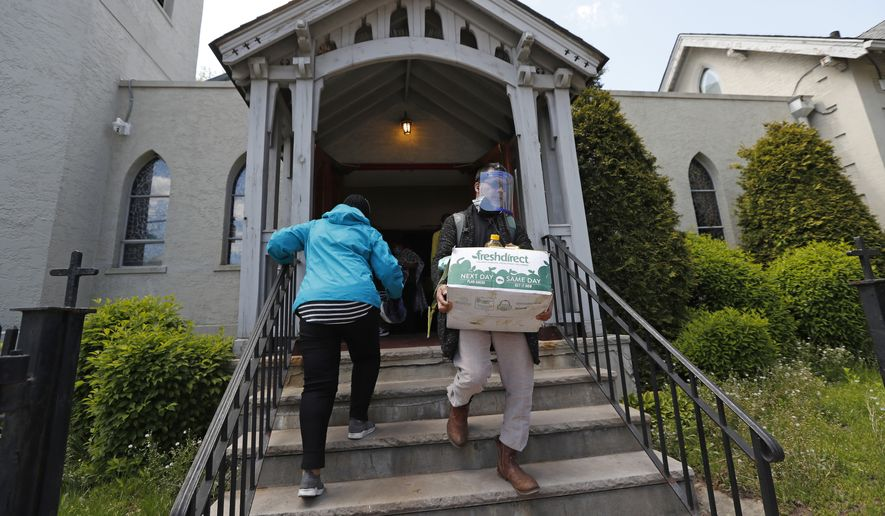 The Rev. Juan Carlos Ruiz, right, a co-founder of the New Sanctuary movement, carries a box of groceries to a woman waiting at the foot of the steps of Lutheran Church of the Good Shepherd in the Bay Ridge neighborhood of the Brooklyn borough of New York, Tuesday, May 12, 2020. Ruiz and others started the Brooklyn Immigrant Community Support mutual aid group in response to a food emergency after many immigrants, including many undocumented workers, were laid off by their employers during the coronavirus outbreak. (AP Photo/Kathy Willens)