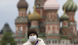 A woman wearing face mask to protect against coronavirus, walks near Red Square with St. Basil's Cathedral in the background in Moscow, Russia, Tuesday, May 12, 2020. (AP Photo/Alexander Zemlianichenko)