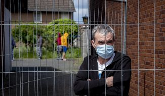 Julian, Romanian worker who stands behind the fence that was set up at the entrance of a housing of Romania slaughterhouse workers in Rosendahl, Germany, Tuesday, May 12, 2020. Hundreds of the workers were tested positive on the coronavirus and were put on quarantine. (AP Photo/Michael Probst)