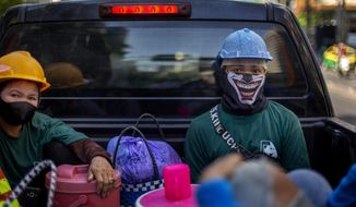 Construction workers wearing face masks travel in a back of a crew cab in Bangkok, Thailand, Wednesday, May 13, 2020. Thai government continue to ease restrictions related to running business in capital Bangkok that were imposed weeks ago to combat the spread of COVID-19. (AP Photo/Gemunu Amarasinghe)