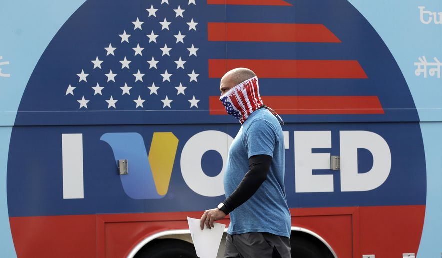 Robb Rehfeld wears a mask as he walks to cast his vote during a special election for California's 25th Congressional District seat Tuesday, May 12, 2020, in Santa Clarita, Calif. Republican Mike Garcia and Democrat Christy Smith are running for the seat after the resignation of Rep. Katie Hill, D-Calif. (AP Photo/Marcio Jose Sanchez)