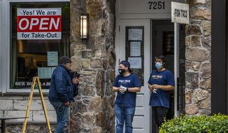 Fish Taco restaurant workers talk to a customer, left, in front of the restaurant in Bethesda, Md., Monday, May 11, 2020. As states push for some return to normal business operations, elected officials in the Virginia and Maryland suburbs surrounding Washington, D.C., are unwilling to quickly reopen, as they confront COVID-19 infection and fatality numbers that are the highest in their states. (AP Photo/Manuel Balce Ceneta)