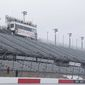 In this Sept. 2, 2016, file photo, workers walk along the grandstands in the rain at Darlington Raceway after weather forced NASCAR to call off qualifying for the Sprint Cup and XFinity series auto races. NASCAR says it will resume its season without fans present starting May 17 at Darlington Raceway in South Carolina. (AP Photo/Terry Renna, File)  **FILE**