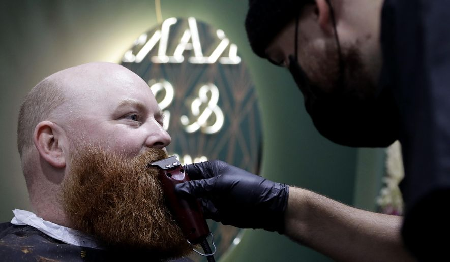 A man has his beard trimmed at a barber in Christchurch, New Zealand, Thursday, May 14, 2020. New Zealand lifted most of its remaining lockdown restrictions from midnight Wednesday as the country prepares for a new normal. Malls, retail stores and restaurants are all reopening Thursday in the South Pacific nation of 5 million, and many people are returning to their workplaces. (AP Photo/Mark Baker)