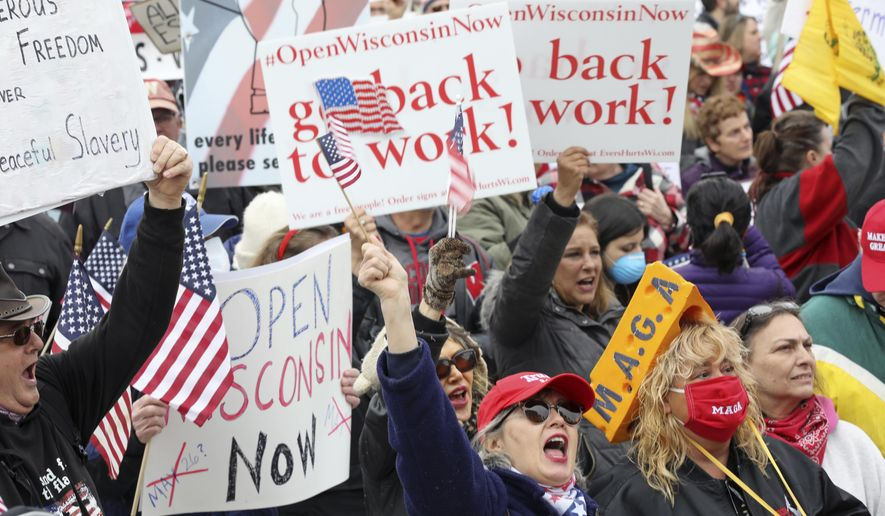 In this April 24, 2020, file photo, protesters gather for a rally against Gov. Tony Evers' extended stay-at-home order due to COVID-19, at the Wisconsin State Capitol in Madison, Wis. The Wisconsin Supreme Court struck down Gov. Evers' coronavirus stay-at-home order Wednesday, May 13, 2020 ruling that his administration overstepped its authority when it extended the mandate for another month without consulting legislators. (Amber Arnold/Wisconsin State Journal via AP, file)