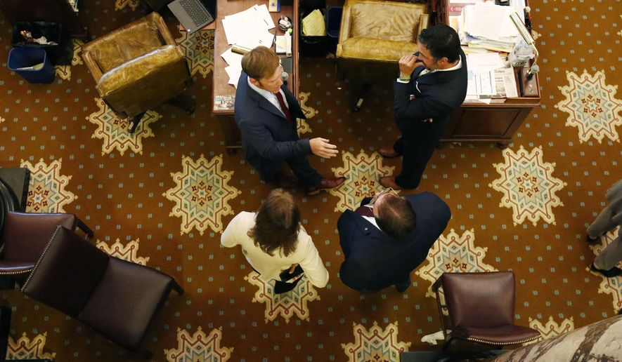 Republican Sens. Philip Moran, bottom right, of Kiln; Melanie Sojourner, bottom left, of Natchez; Chris McDaniel, top right,  of Ellisville; and Neil Whaley, of Potts Camp, wait to vote on a coronavirus relief bill for small businesses, Wednesday afternoon, May 13, 2020, at the Capitol in Jackson, Miss. (AP Photo/Rogelio V. Solis)