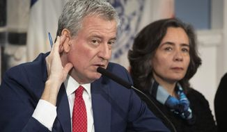 """In this Feb. 26, 2020 file photo, Mayor Bill de Blasio, left, with Dr. Oxiris Barbot, commissioner of the New York City Department of Health and Mental Hygiene, listens to a reporter's question in New York. DeBlasio says he's investigating a report that the city's health commissioner spoke dismissively of the health concerns of police officers during a heated phone call with a top police commander in the early days of the coronavirus crisis. The Mayor said he wants to speak with Barbot and NYPD Chief of Department Terence Monahan to """"understand exactly what happened"""" during the exchange in late March. (AP Photo/Mark Lennihan, File)"""