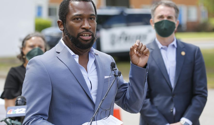 In this Tuesday May 12, 2020 photo, Richmond Mayor Levar Stoney, left, gestures as Virginia Gov. Ralph Northam, right, listens during an event with a group of volunteers to distribute supplies at health equity community event in Richmond, Va. The City of Richmond and Accomack County, which is on the state's Eastern Shore, have both asked Northam to delay a gradual reopening of some nonessential businesses. (AP Photo/Steve Helber)