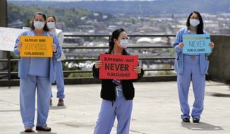 Health care workers Mechelle Cannon, left, Chiow Saechao and Gina Tualla stand in protest with other staff at Harborview Medical Center, a part of UW Medicine, during a noon hour break in a demonstration asking management to do more to protect staff, patients and the public amid the COVID-19 pandemic, Thursday, May 14, 2020, in Seattle. Protest organizers said UW Medicine has failed to fully implement public health guidance designed to flatten the curve, including proper notification to staff regarding exposure, the installation of sneeze guards to protect staff and the public, and the distribution of personal protective equipment, and has refused to extend agreements with unions that provide economic protections for employees. (AP Photo/Elaine Thompson)
