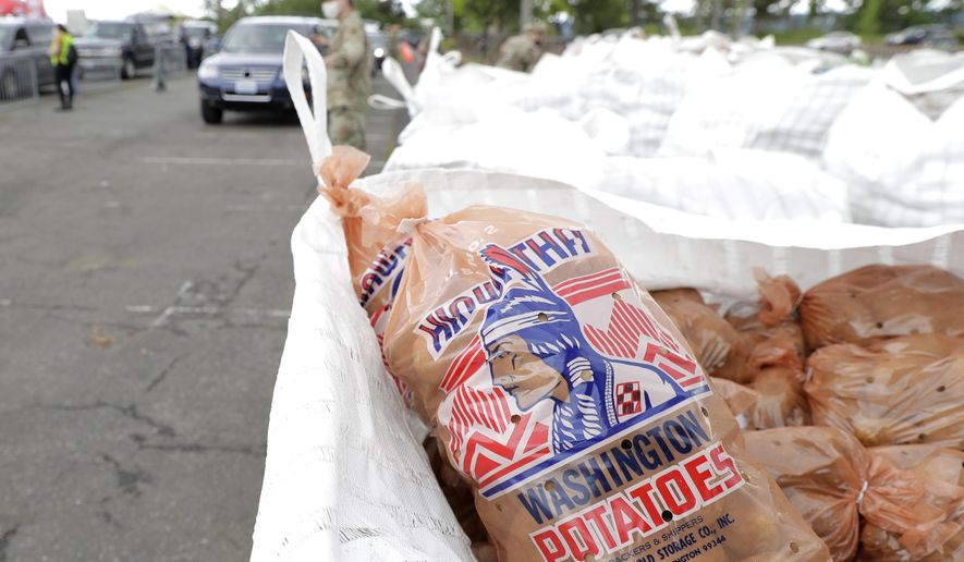 A bag of potatoes grown in Washington sits on a pallet Thursday, May 14, 2020, during the free distribution of 200,000 pounds of potatoes provided by the Washington State Potato Commission in Tacoma, Wash. Most of the potatoes were donated by farmers across the state who have not been able to sell to their regular restaurant customers due to the coronavirus pandemic. (AP Photo/Ted S. Warren)