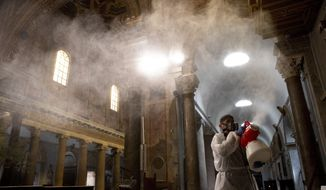 A man sprays disinfectant as he sanitizes Santa Maria in Trastevere Basilica to prevent the spread of the COVID-19 coronavirus, in Rome Wednesday, May 13, 2020. Italy partially lifted lockdown restrictions last week after a two-month lockdown and from May 18 churches are expected to reopen to the public for masses. (AP Photo/Alessandra Tarantino)