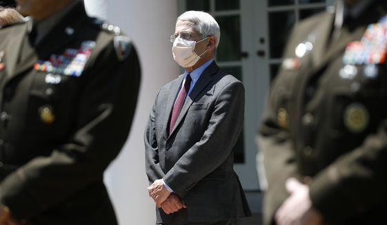Dr. Anthony Fauci, director of the National Institute of Allergy and Infectious Diseases, listens as President Donald Trump speaks about the coronavirus in the Rose Garden of the White House, Friday, May 15, 2020, in Washington. (AP Photo/Alex Brandon)