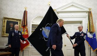 Chief of Space Operations at U.S. Space Force Gen. John Raymond, left, and Chief Master Sgt. Roger Towberman, right, hold the United States Space Force flag as President Donald Trump walks past it in the Oval Office of the White House, Friday, May 15, 2020, in Washington. (AP Photo/Alex Brandon) ** FILE **