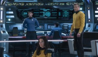 """This image released by CBS All Access shows, from left, Ethan Peck as Spock, Rebecca Romijn as Number One, and Anson Mount as Captain Pike of the the CBS All Access series """"Star Trek: Strange New Worlds."""" CBS All Access is bringing back Spock for its third full live action show in the """"Star Trek"""" universe, ordering a new series set in the years before Capt. James T. Kirk helmed the U.S.S. Enterprise. (Michael Gibson/CBS via AP)"""