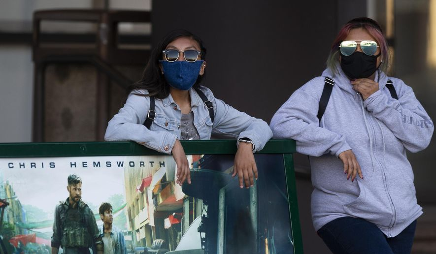 People wear masks as they wait for a bus in Los Angeles on Thursday, May 14, 2020. Leaving home in Los Angeles now requires bringing a face covering. Mayor Eric Garcetti said everyone must carry the coverings when they go outdoors and wear them when they are around people from outside their households. (AP Photo/Damian Dovarganes)