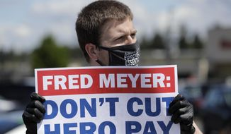 """Sherman Jenne, a cashier at the Fred Meyer grocery store in Burien, Wash., takes part in a protest outside the store against Fred Meyer's parent company Kroger, Friday, May 15, 2020, that was organized by the United Food and Commercial Workers International Union. Kroger officials have said they are ending the additional $2 hourly """"hero pay"""" bonus that had been paid to workers since late March during the coronavirus pandemic. The company said Friday it will now offer one-time bonus payments of $400 and $200 for full- and part-time employees to be paid in two installments. (AP Photo/Ted S. Warren)"""