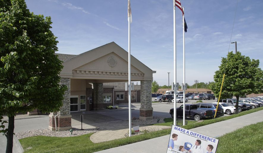 A flag flies Friday, May 15, 2020, on the grounds of the Life Care Center nursing and rehabilitation facility in Elkhorn, a suburb of Omaha, Neb., where a large number of staff and residents tested positive for COVID-19. (AP Photo/Nati Harnik)