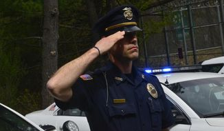 Members of the Brattleboro Police Department, in Brattleboro, Vt., line up in formation to salute the American flag during a moment of silence held for Vermont's fallen law enforcement officers across the state on Friday, May 15, 2020. (Kristopher Radder/The Brattleboro Reformer via AP)