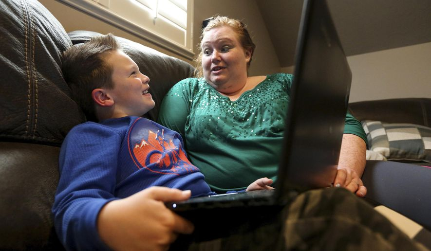 In this Thursday, March 5, 2020, photo, Lucas West, 7, participates in Applied Behavior Analysis therapy with Chelsey Bodily, a board-certified behavior analyst, at his home in Layton, Utah. (Ivy Ceballo/The Deseret News via AP)
