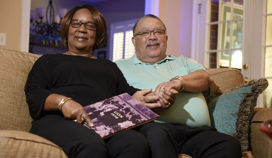 In this Friday, May 1, 2020 photo, Patricia and Terry Elam pose at their home in Augusta, Ga. The couple were students at Paine College during the 1970 riot in Augusta when they had to flee the college during the unrest 50 years ago. (Michael Holahan/The Augusta Chronicle via AP)