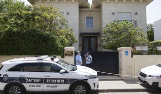Israeli police officers stand outside the residence of the Chinese ambassador, in the central Israeli city of Herzliya, Sunday, May 17, 2020. Du Wei, 58, who was appointed envoy in February in the midst of the coronavirus pandemic, was found dead in his home north of Tel Aviv on Sunday, Israel's Foreign Ministry said. No cause of death was given and Israeli police said it was investigating. (AP Photo/Sebastian Scheiner)